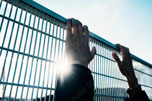 man climbing up a metal fence Wallpaper Mural