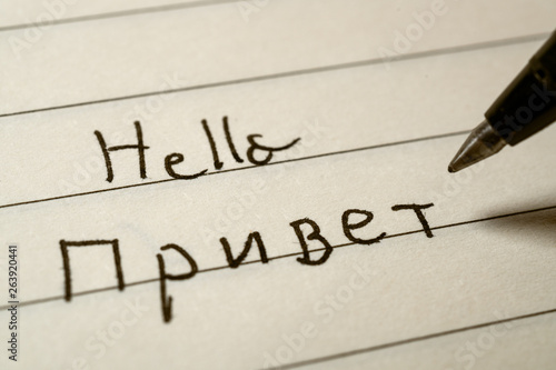 Fotografie, Obraz  Beginner Russian language learner writing Hello word in Russian cyrillic alphabe