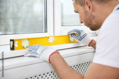 Construction worker using bubble level while installing window indoors Canvas Print