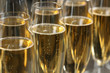 Many glasses of champagne as background, closeup view