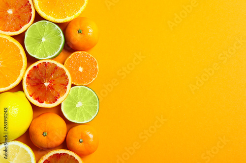 Different citrus fruits on color background, flat lay. Space for text