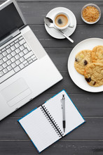Portrait View Of A Laptop, Coffee, Cookies, Sugar  And Note Pad On A Dark Wooden Background
