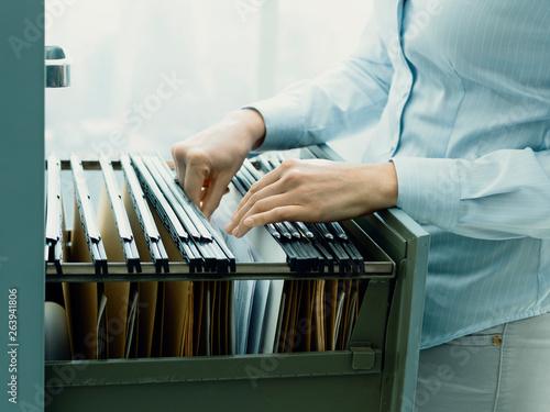 Obraz na plátně Office clerk searching files in the filing cabinet