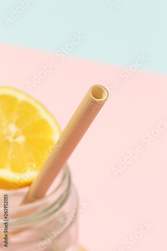 Bamboo straw in a glass of lemon water on the pink