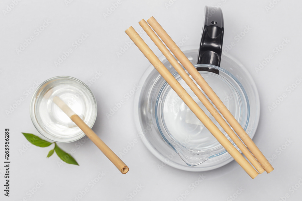Bamboo straw in a glass of water on the grey background, Reusable bamboo straws as an alternative for single-use plastic straws, healthy and sustainable lifestyle concept