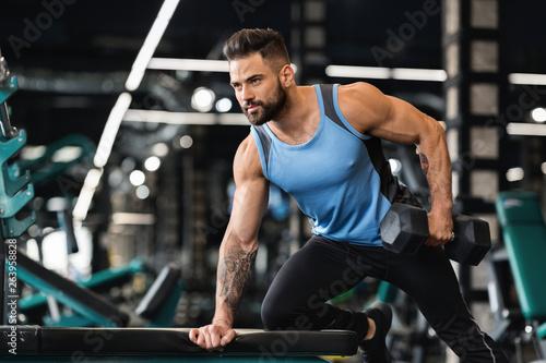 Fotografia  Millennial muscular man doing exercises with dumbbells
