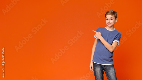 Fotografía  Cute little boy pointing away on orange background