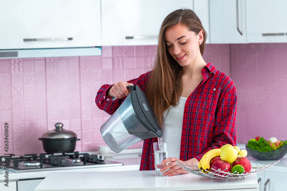 Fototapeta Young woman pouring fresh filtered water from water filter into a glass for drink at kitchen. Water purification at home