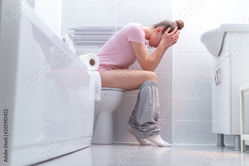 Fotografía Ill, unwell woman suffering from diarrhea, constipation and stomach pain at toilet