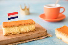 Orange Tompouce, Traditional Dutch Treat With Pudding And Frosting On National Holiday Kings Day (April 27th), In The Netherlands. With Cup Of Coffee, Crown And Dutch Flag