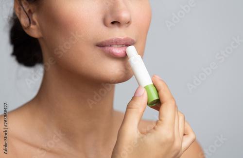 Lips nutrition. Girl applying hygienic balm over grey background Fototapeta