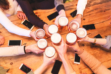 Friends Drinking And Toasting Beer At Pub