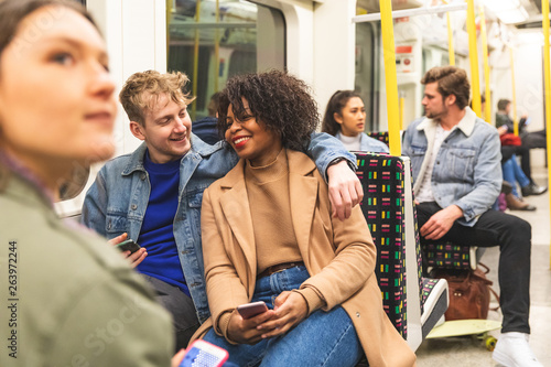 Multiracial couple travelling by tube together Canvas Print