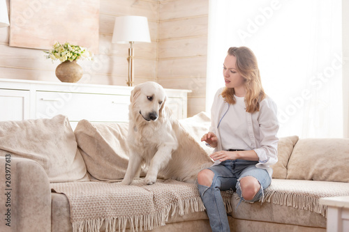 Young handsome woman teaches his big dog to the rules sitting on the sofa in the living room of his country house Canvas Print