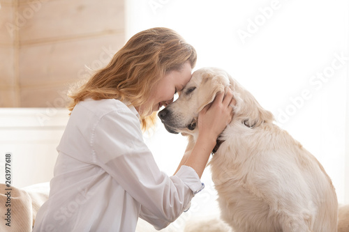 Fotografía Young pretty woman in casual clothes hugging her beloved big white dog sitting on the sofa in the living room of her cozy country house