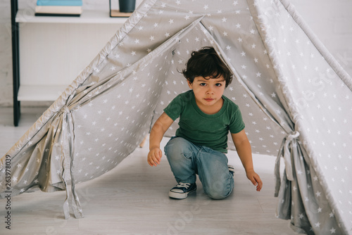 cute kid in jeans sitting in grey wigwam at home Fotobehang