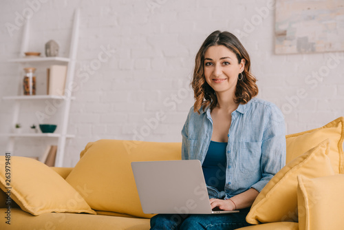 Attractive smiling freelancer sitting on yellow sofa and using laptop