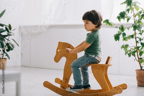 Valokuva child sitting on wooden rocking horse in living room