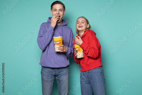 Photo  Young happy couple in casual clothes standing isolated over blue background