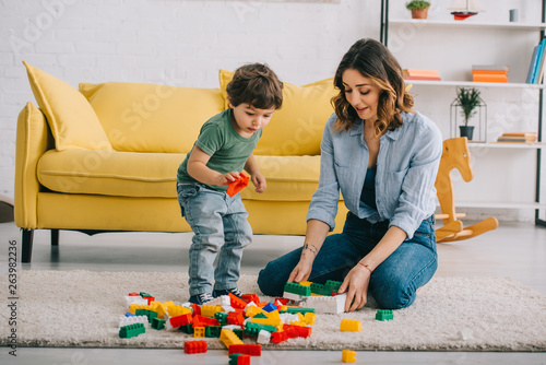 Obraz Mother and son playing with lego on carpet in living room - fototapety do salonu