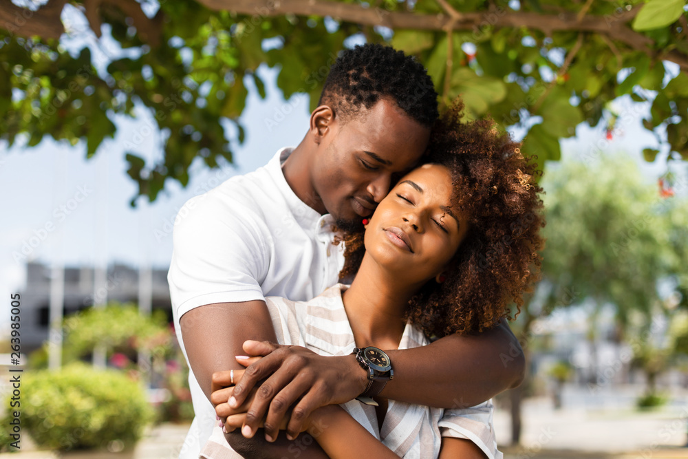 Fototapeta Outdoor protrait of black african american couple embracing each other