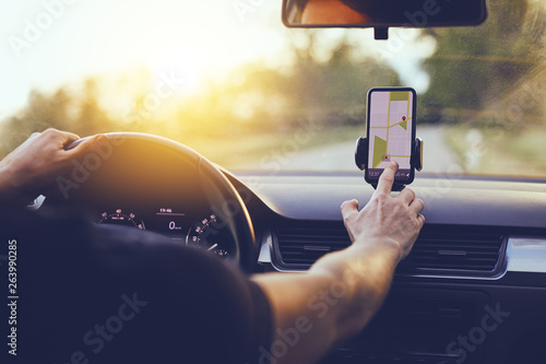 Driver using GPS navigation in mobile phone while driving car at sunset