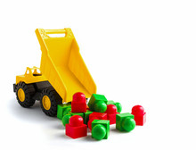 Yellow Dump Truck Toy Unload Colorful Plastic Blocks On White Background