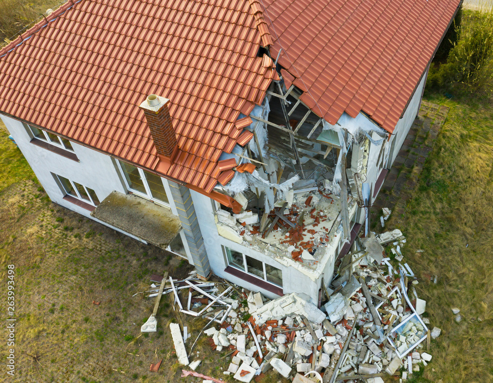 Fototapeta Aerial view on damaged red single house roof after strong wind or explosion. Hole in the rooftop and floor. Rubble on the ground