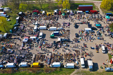 Aerial View On Flea Market With Miscellaneous Items And Crowds Of Buyers And Seller's Makeshift Stands