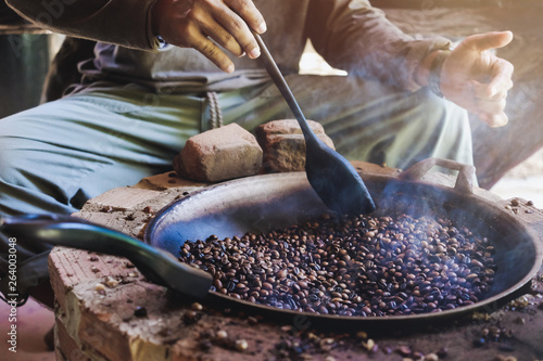 Fotografía Asian men are sitting roasting coffee beans in a pan on an antique stove
