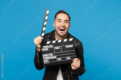 Canvas Print Handsome stylish young unshaven man in black jacket white t-shirt hold in hand film making clapperboard isolated on blue wall background studio portrait