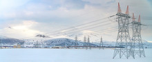 High Voltage Towers With Blue Sky And Snowy Landscape Background