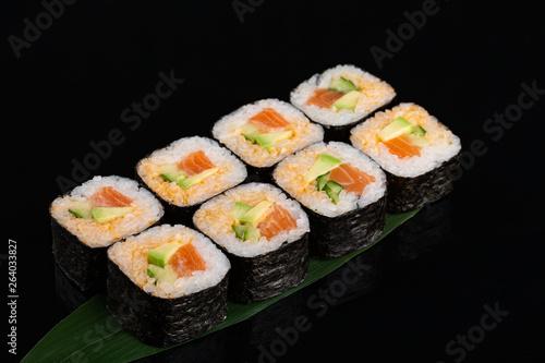 Fototapeta Maki sushi with avocado, cucumber and salmon on banana leaf obraz