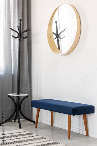 Fototapety, obrazy: Coat hanger, blue settee and round mirror in wooden frame in spacious hall