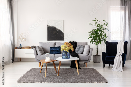 Fototapety, obrazy: Flowers in blue glass vase and two white candles on wooden coffee tables in grey elegant living room with comfortable sofa