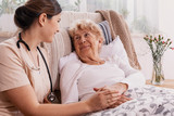 Positive senior woman lying in bed, helpful doctor in beige uniform supporting her - 264034646