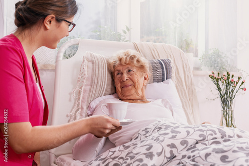 Positive senior patient lying in hospital bed with helpful nurse in pink uniform at her site