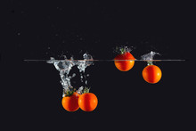 Cherry Tomatoes Dipped In Water Splash On Black Background