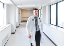 Doctor In A White Coat Walking Down A Hallway In A Hospital.