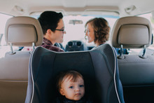 Mom And Dad Driving In White Car With Baby In A Car Seat In The Back