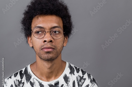 Photo Portrait of a curly African man with glasses on a gray background