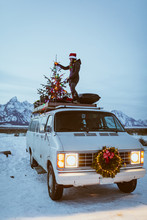 Young Woman Stands On Vintage White Van With Christmas Tree
