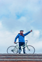Front View Of Senior Man Casual Clothing Holding Bike, Pointing Away