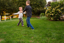 Two Small Boys Play Together In Yard