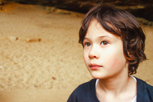 Portrait Of A Small Boy Standing Outside In Golden Light Looking Up