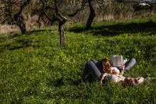 Two Young Girls Lying In The Field Read A Book