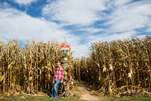 Smiling Tween Boy In Red Shirt Stands At Entrance To Corn Maze