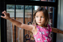 A Little Girl Stands At An Open Doorway Looking Off Into The Distance