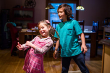 Portrait Of Happy Siblings Dancing Together At Home