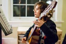 A Boy Studies Sheet Music As He Practices Guitar